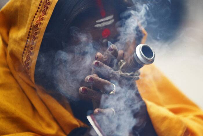 "A sadhu woman smokes marijuana during the ""Shivaratri"" festival at the courtyard of the Pashupatinath Hindu temple in Nepal. (AP)"