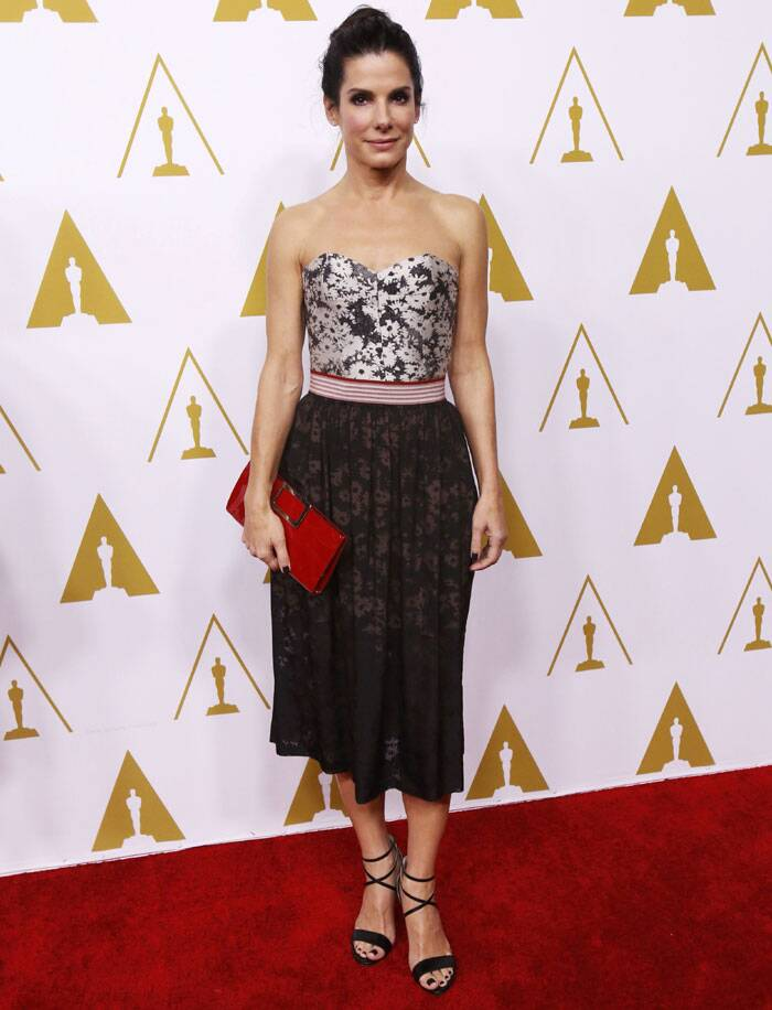 Oscar winner and nominee Sandra Bullock opted for a floral printed dress with different coloured top and skirt. She added colour to her look with red clutch. (AP)