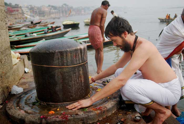 A foreigner is seen worshipping of Lord Shiva at the bank of River Ganga on the eve of Maha Shivratri in Varanasi. (PTI)