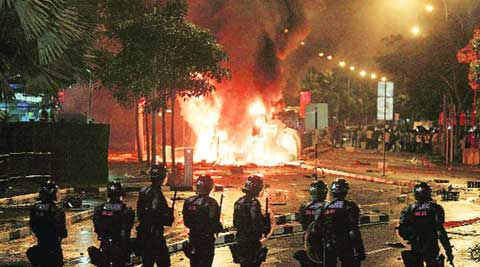 Singapore police watch as protestors burn a bus in Little India.