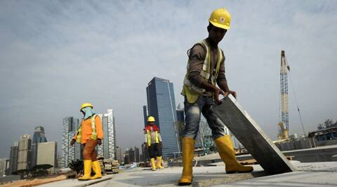 Migrant workers from India construct a road leading to the Financial District, background, in Singapore. (AP)