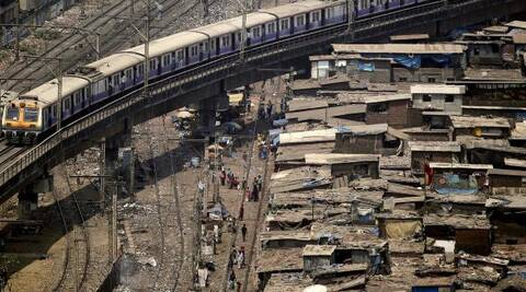 A local train moves on an elevated track over a slum area in Mumbai. (AP)