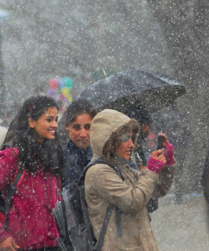 Young girls enjoy the snowfall in Shimla on Thursday. (PTI)