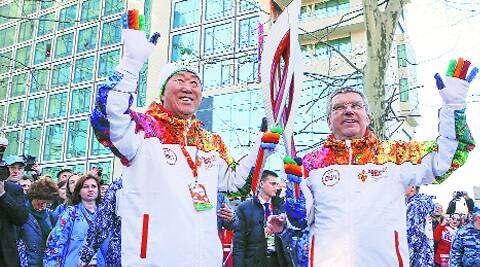 IOC President Thomas Bach (right) hands over the 2014 Sochi Olympics torch to UN Secretary-General Ban Ki-moon as the relay arrived in Sochi Thursday. (Reuters)
