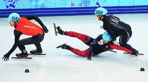 Charles Hamelin of Canada(C) fell in the 1,000 meters and took out Eddy Alvarez (2nd R) of USA. The skaters in first and second place get a pass after a collision; Alvarez was in third. (AP)