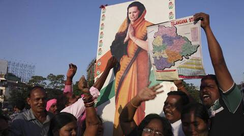 People celebrate with a photograph of Congress party president Sonia Gandhi after the Indian parliament's lower house passed the bill for the creation of new state called 'Telangana' in Hyderabad.