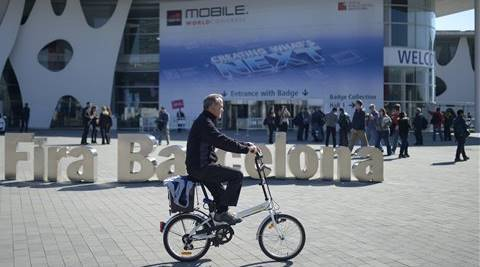 A man rides his bicycle outside the Mobile World Congress, the world's largest mobile phone trade show in Barcelona. (Photo: AP)