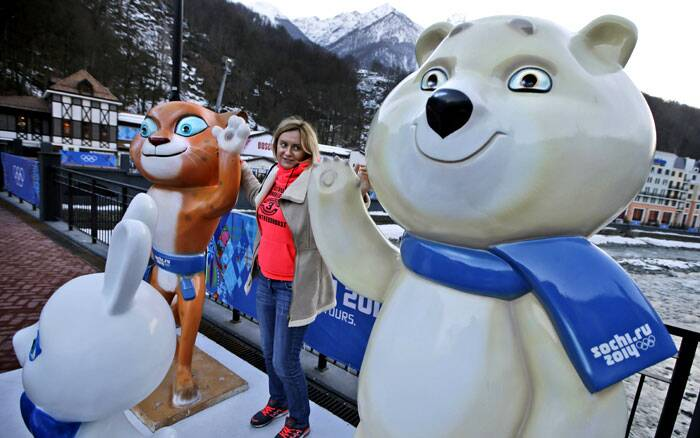 A woman poses for pictures with the mascots of the 2014 Winter Olympics in Krasnaya Polyana, Russia. (AP)