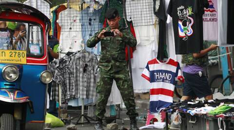 A soldier photographs the scene of an explosion littered with blood and small pairs of shoes at a main protest site in Bangkok. (AP)