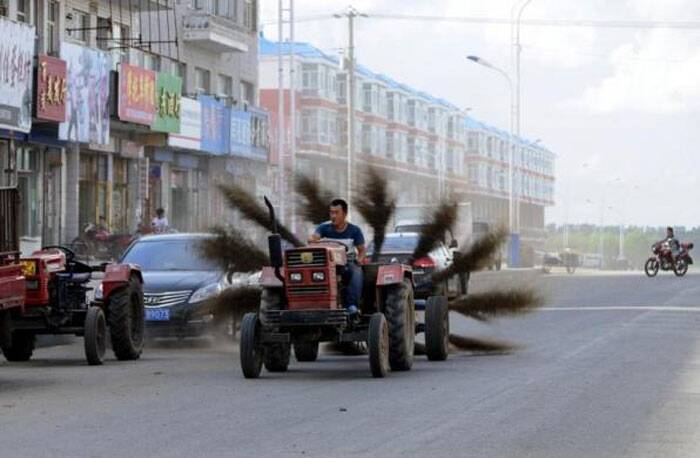 A man drives an improvised tractor with 12 brooms tied in the rear, as he tries to clean a road in Mohe, Heilongjiang province, August 31, 2013. (Reuters)