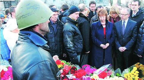 """European Union foreign policy chief Catherine Ashton (2nd R) visits a memorial for victims of last week's clashes in Kiev Monday; (inset) a """"Wanted"""" notice of fugitive President Victor Yanukovych. Reuters"""