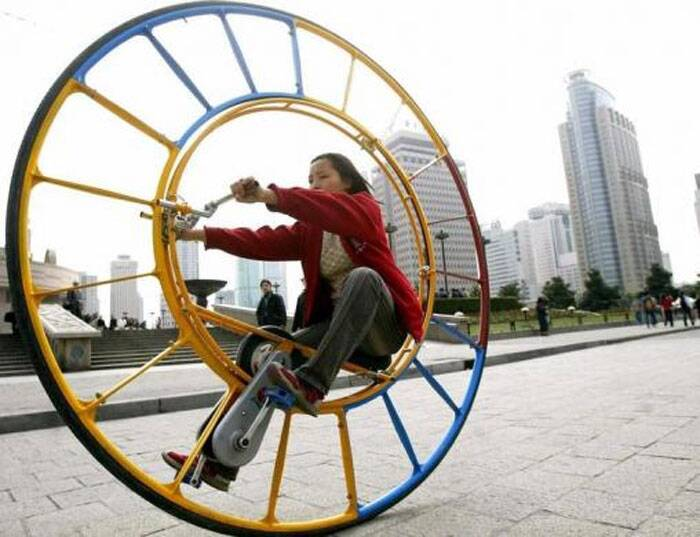 "A woman rides an unicycle at a park in Shanghai February 28, 2004. The unicycle was designed by Chinese inventor Li Yongli who called it ""the number one vehicle in the world."" (Reuters)"