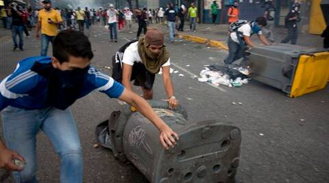 Demonstrators push garbage cans to build a barricade on a road in the Altamira neighborhood of Caracas, Venezuela, Wednesday, Feb. 19, 2014. (AP)
