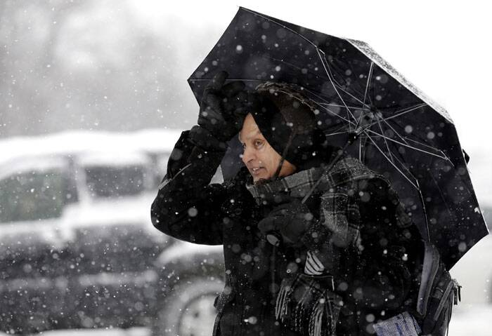 Usuddin Shaikh holds an umbrella as he waits for a bus during a heavy snowy day in Morton Grove. (AP)