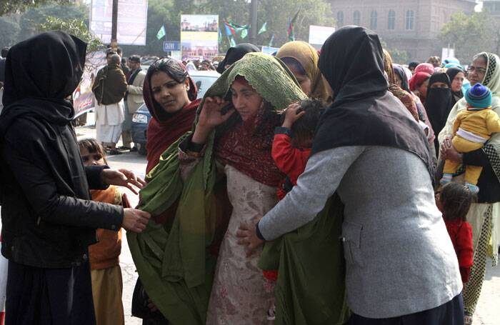 Pakistani police officers search participants at a rally to mark Kashmir Day, in Lahore. (AP)