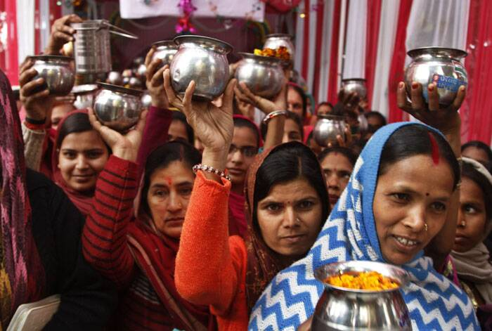 Hindu devotees wait with pots of water to offer prayers to Lord Shiva on the occasion of Shivaratri festival in Jammu. (AP)