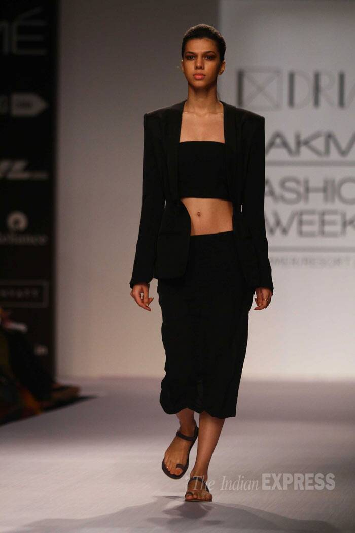 A model walks down the ramp in a black bustier with a pencil skirt and blazer. (IE Photo: Amit Chakravarty)