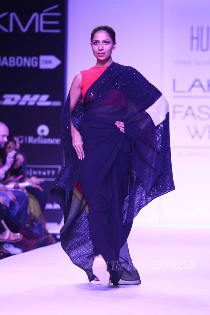 A model takes to the ramp in a dark coloured draped sari over a bright orange blouse. (IE Photo: Amit Chakravarty)