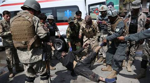 Afghan army and police officers move the body of an insurgent from the scene after the Taliban staged an attack on a police station in Jalalabad on Thursday. (AP)