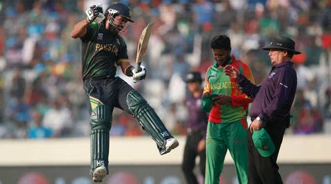 Umpire Ian Gould had to take evasive action as Shehzad celebrated reaching the three-figure mark (AP)