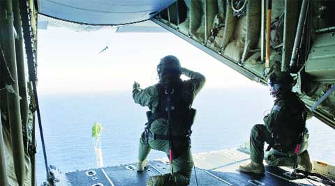 RAAF loadmasters launch a 'self-locating data marker buoy' from a C-130J Hercules aircraft in the southern Indian Ocean