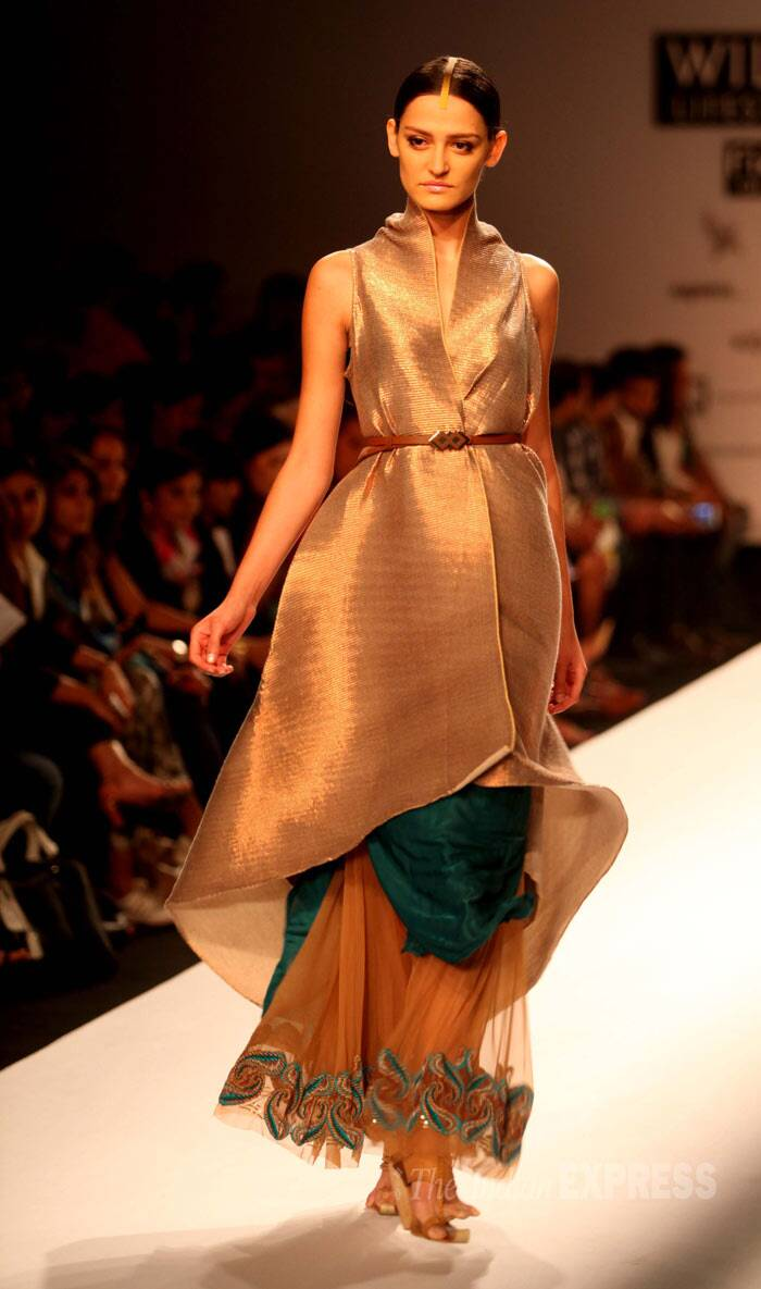 A model walks the ramp in a stunning muted gold design for Kiran Uttam. (IE Photo: Amit Mehra)