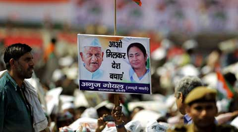 A supporter holds a placard with portraits  of Mamata Banerjee and social activist Anna Hazare during an election rally addressed by Banerjee in New Delhi. (PTI)