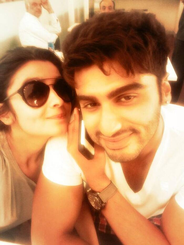 "Keeping up with the selfie mania, Bollywood actress Alia Bhatt posted a selfie with her rumoured beau and '2 States' co-star Arjun Kapoor. Arjun, who was busy in a telephonic interview, nevertheless smiled for pretty Alia, who is clearly in a cheery mood. Alia captioned the pic, ""Trying to take a selfie during Arjun's interview!"""