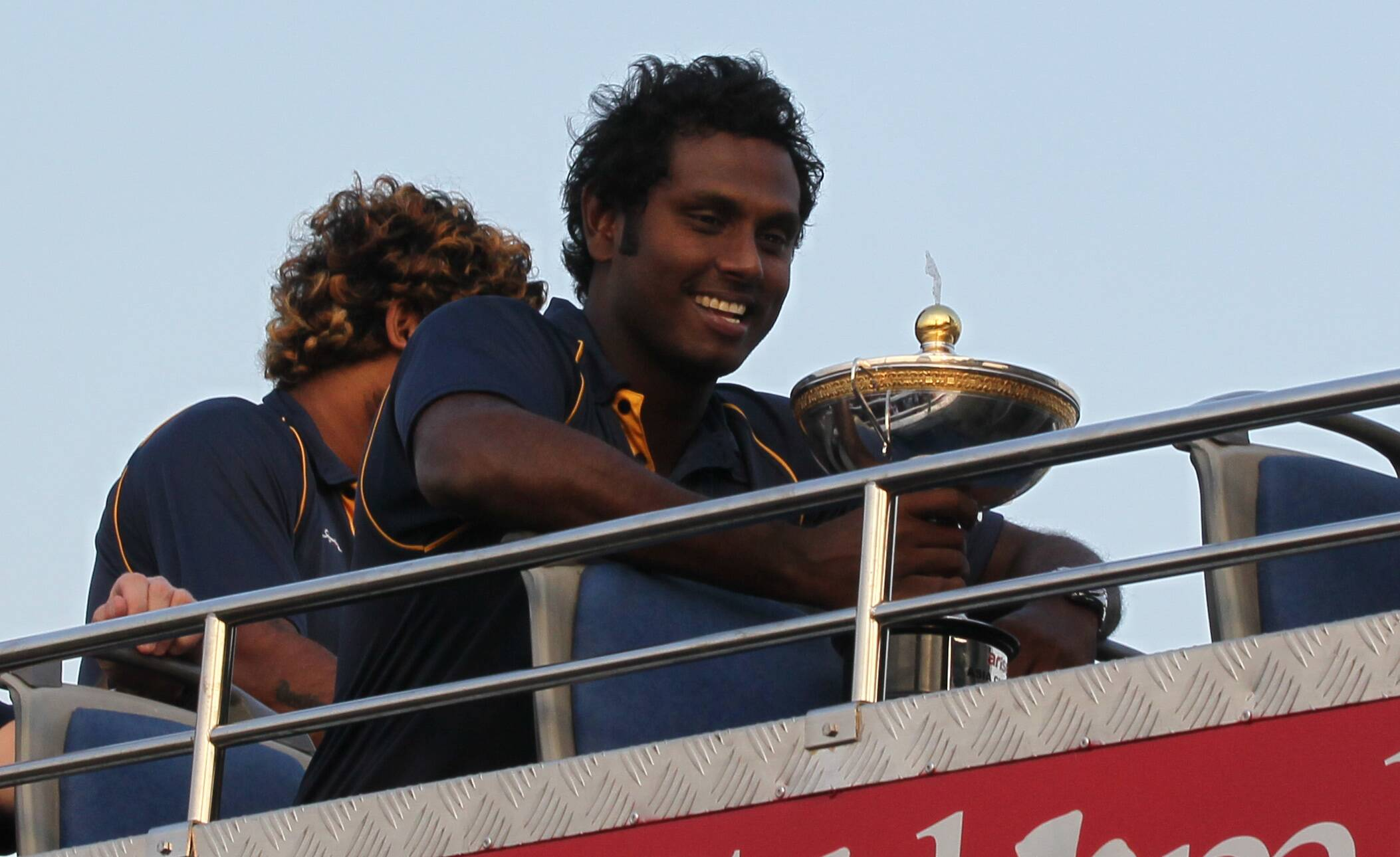 Sri Lankan cricket captain Angelo Mathews, right, smiles holding cup as he sits in an open bus with team mate Lasith Malinga, left,  upon their return from Bangladesh after winning the Asia Cup in Colombo, Sri Lanka, Sunday, March 9, 2014. Sri Lanka Saturday won the Asia Cup tournament defeating Pakistan by 5 wickets.  (AP Photo/Eranga Jayawardena)
