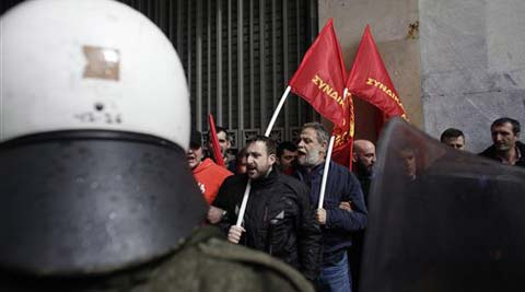 Protesters affiliated to the Communist Party shout slogans as riot policemen block them during a demonstration against austerity measures in Athens, on Thursday March 6, 2014. (AP)