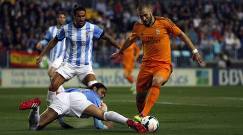 Real Madrid's Karim Benzema (R) battles for the ball with Malaga's Sergio Sanchez during their Spanish First Division soccer match at La Rosaleda stadium in Malaga, southern Spain. (Reuters)