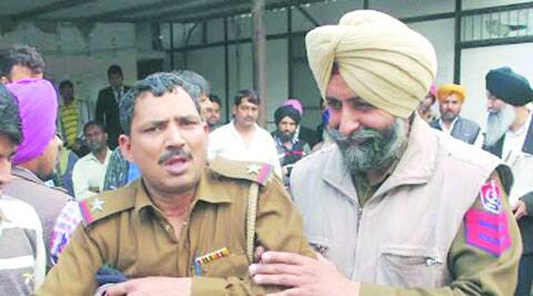 Drunk ASI Jagdish Kumar (left) being detained by Mohali police on Tuesday. Express