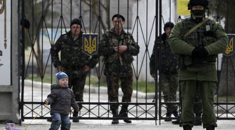 A child plays near a Russian soldier, right, while Ukrainian soldiers look on from behind gates as the Russian soldier guards the gate of an Ukrainian infantry base in Perevalne, Ukraine. (AP)