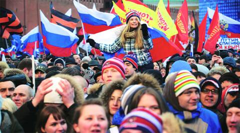 People at a rally in support of Crimea joining Russia, celebrate holding Russian flags at Red Square in Moscow Tuesday. AP