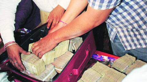 Traders deposit cash during the draw-of-lots of liquor vends in Ludhiana on Saturday. Gurmeet Singh