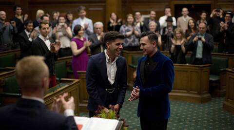 Sean Adl-Tabatabai, left, and Sinclair Treadway are applauded by their guests as they were announced officially married during a wedding ceremony in the Council Chamber at Camden Town Hall in London. (AP)
