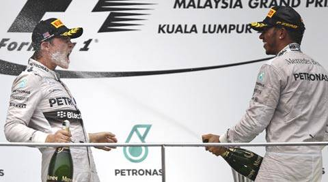Mercedes driver Lewis Hamilton, right, of Britain sprays champagne to his teammate Nico Rosberg during the prize presentation on the podium after the Malaysian Formula One Grand Prix at Sepang International Circuit (AP)