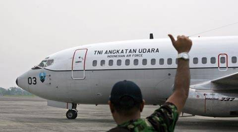 "A ground crew gives an 'OK' sign to the pilots of an Indonesian Air Force Boeing 737 ""Surveiller"" of the 5th Air Squadron ""Black Mermaids"" as they prepare to take off for a search operation for the missing Malaysia Airlines jetliner. (AP)"