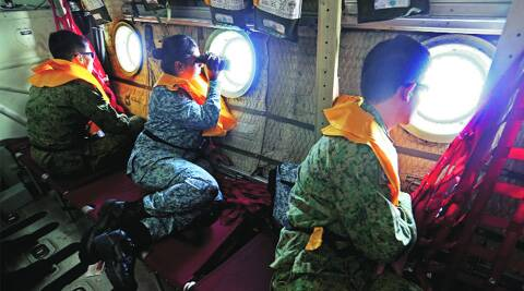 Military personnel look out of a Republic of Singapore Air Force (RSAF) C130 transport plane as they search for the missing Malaysia Airlines MH370 plane over the South China Sea Tuesday. (REUTERS)