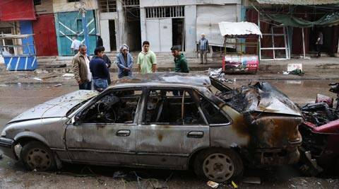 People inspect the site of a car bomb explosion in Baghdad's northern Qahirah neighborhood, Iraq. (AP)
