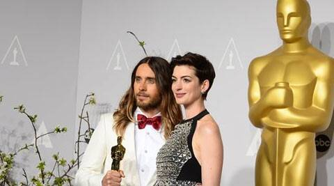 "Jared Leto, left, poses with his award for best supporting actor for his role in ""Dallas Buyers Club"" with Anne Hathaway during the Oscars. (AP)"