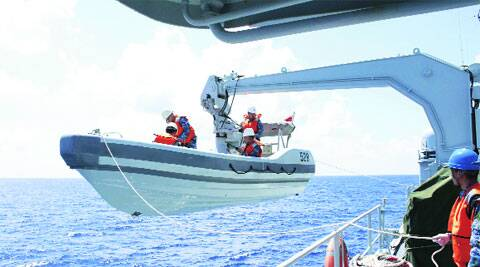 A search boat carrying rescue workers is set down from Mianyang warship on the suspected crash site