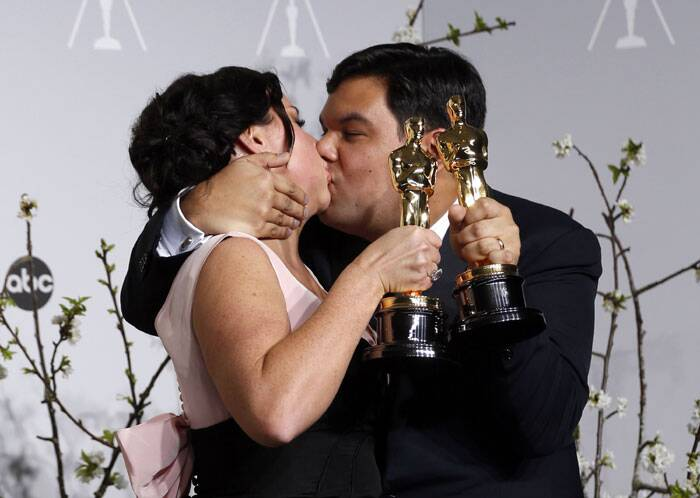 Kristen Anderson-Lopez and Robert Lopez lock lips after they win an Oscar for their composition 'Let it Go'.