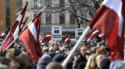 People carry Latvian flags as they march to the Freedom Monument to commemorate World War II veterans. (AP)