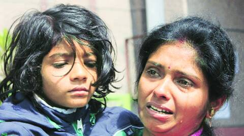 A mother cries after she fails to get her daughter admitted to King George's Medical University Hospital in Lucknow. PTI