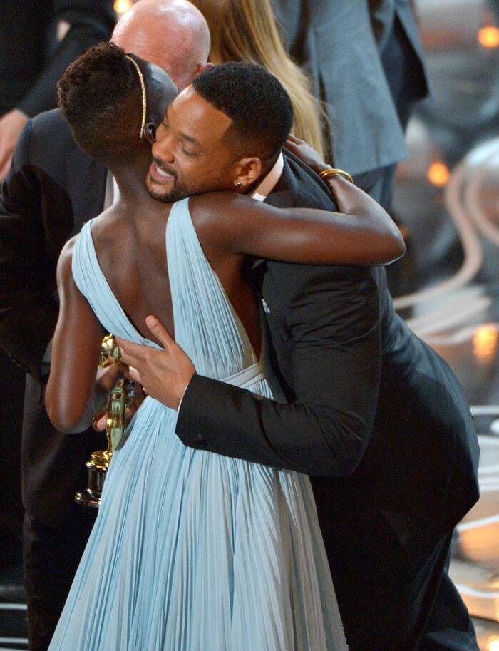 Will Smith gives Lupita Nyong'o a hug, congratulating her Oscar win.