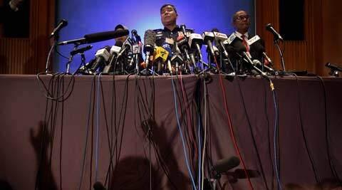 Over a dozen microphones are propped on a table as Malaysian police chief Khalid Abu Bakar answers questions from members of the media. (AP)