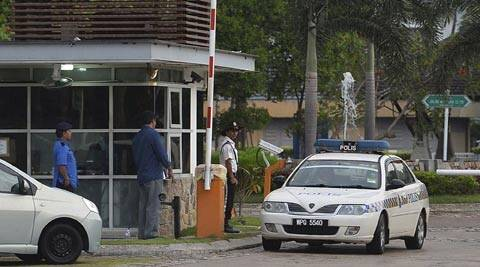 A police car comes out of a main gate of the missing Malaysia Airlines pilot Zaharie Ahmad Shah's house in Shah Alam, outside Kuala Lumpur. (AP Photo)