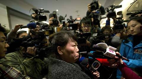 A Chinese relative of passengers aboard a missing Malaysia Airlines plane is surrounded by media as she answers questions about how families are being compensated outside a hotel room. (AP)