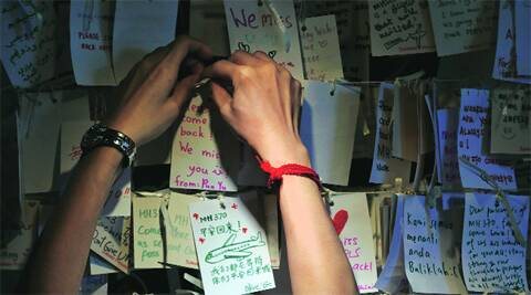A woman hangs a message for MH370 passengers at a Kuala Lumpur mall Saturday. reuters